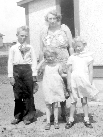 Grandma and her three children in front of the tiny house in Benson